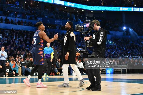 Dennis Smith Jr. #5 of the New York Knicks exchanges handshakes with Dwyane Wade of the Miami Heat during the 2019 AT&T Slam Dunk Contest during the...
