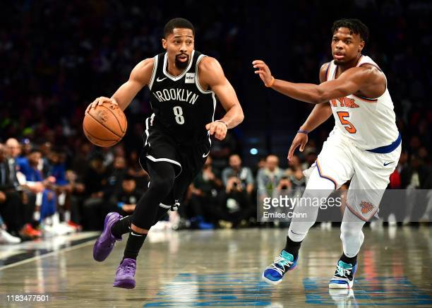 Dennis Smith Jr #5 of the New York Knicks guards Spencer Dinwiddie of the Brooklyn Nets as he dribbles the ball during the first half of their game...