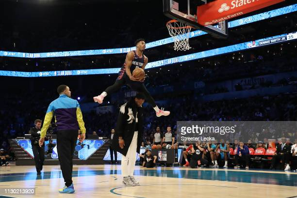 Dennis Smith Jr #5 of the New York Knicks jumps over Dwyane Wade as he dunks during the ATT Slam Dunk as part of the 2019 NBA AllStar Weekend at...
