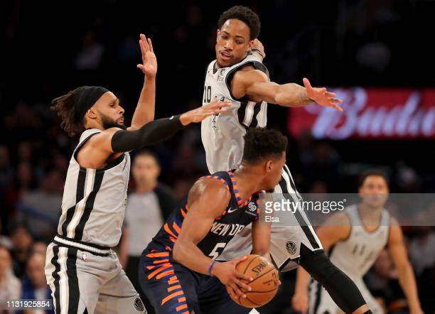 Dennis Smith Jr #5 of the New York Knicks tries to get around Patty Mills and DeMar DeRozan of the San Antonio Spurs at Madison Square Garden on...