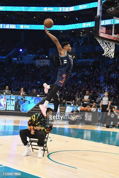 Dennis Smith Jr jumps over J Cole to shoot the ball at the ATT Slam Dunk during the 2019 State Farm AllStar Saturday Night at Spectrum Center on...