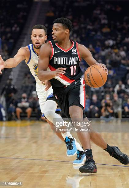 Dennis Smith Jr of the Portland Trail Blazers drives past Stephen Curry of the Golden State Warriors during the first half of their game at Chase...