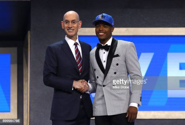 Dennis Smith Jr walks on stage with NBA commissioner Adam Silver after being drafted ninth overall by the Dallas Mavericks during the first round of...