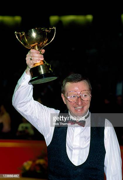 Dennis Taylor of Northen Ireland holds aloft the trophy after defeating Alex Higgins of Northern Ireland 98 in the Masters Snooker Championship Final...