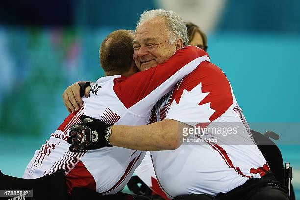 Dennis Thiessen celebrates with Jim Armstrong of Canada after winning the gold medal match between Russia and Canada on day eight of Sochi 2014...