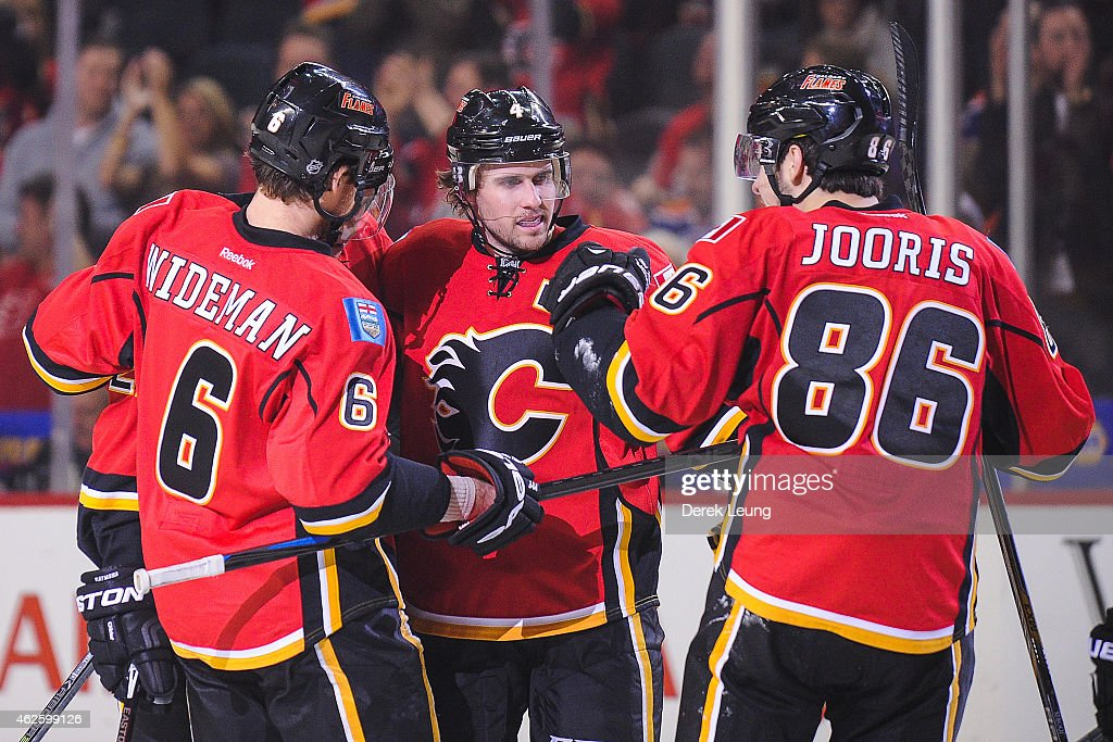 Dennis Wideman #6, Kris Russell #4, and Josh Jooris #86 of the Calgary Flames celebrate their teammate Paul Byron's (not pictured) goal against the Edmonton Oilers during an NHL game at Scotiabank Saddledome on January 31, 2015 in Calgary, Alberta, Canada. The Flames defeated the Oilers 4-2.