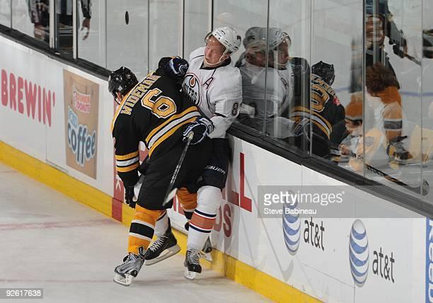 Dennis Wideman of the Boston Bruins checks against Ales Hemsky of the Edmonton Oilers at the TD Garden on October 31 2009 in Boston Massachusetts