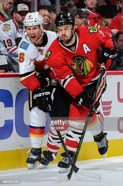 Dennis Wideman of the Calgary Flames and Brent Seabrook of the Chicago Blackhawks skate around the boards in the third period of the NHL game at the...