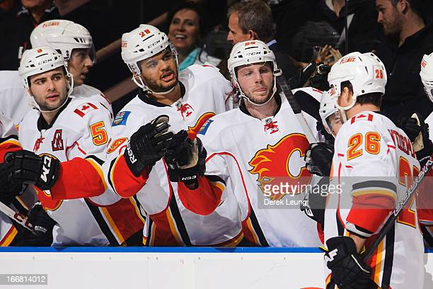 Dennis Wideman of the Calgary Flames celebrates a goal with teammates Max Reinhart and Akim Aliu during their game against the Edmonton Oilers at...