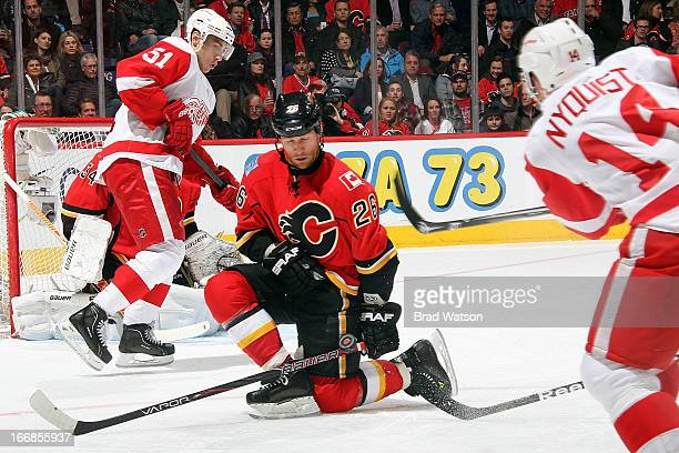 Dennis Wideman of the Calgary Flames kneels to block a shot from Gustav Nyquist of the Detroit Red Wings on April 17 2013 at the Scotiabank...