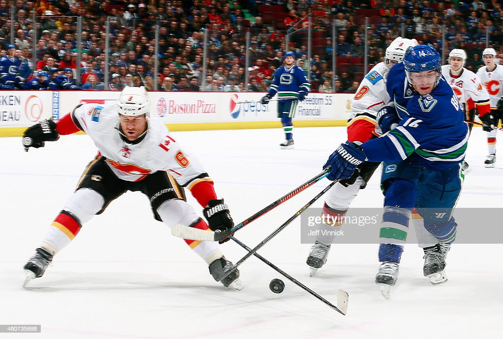 Dennis Wideman #6 of the Calgary Flames reaches too redirect a pass from Alexandre Burrows #14 of the Vancouver Canucks during their NHL game at Rogers Arena December 20, 2014 in Vancouver, British Columbia, Canada.