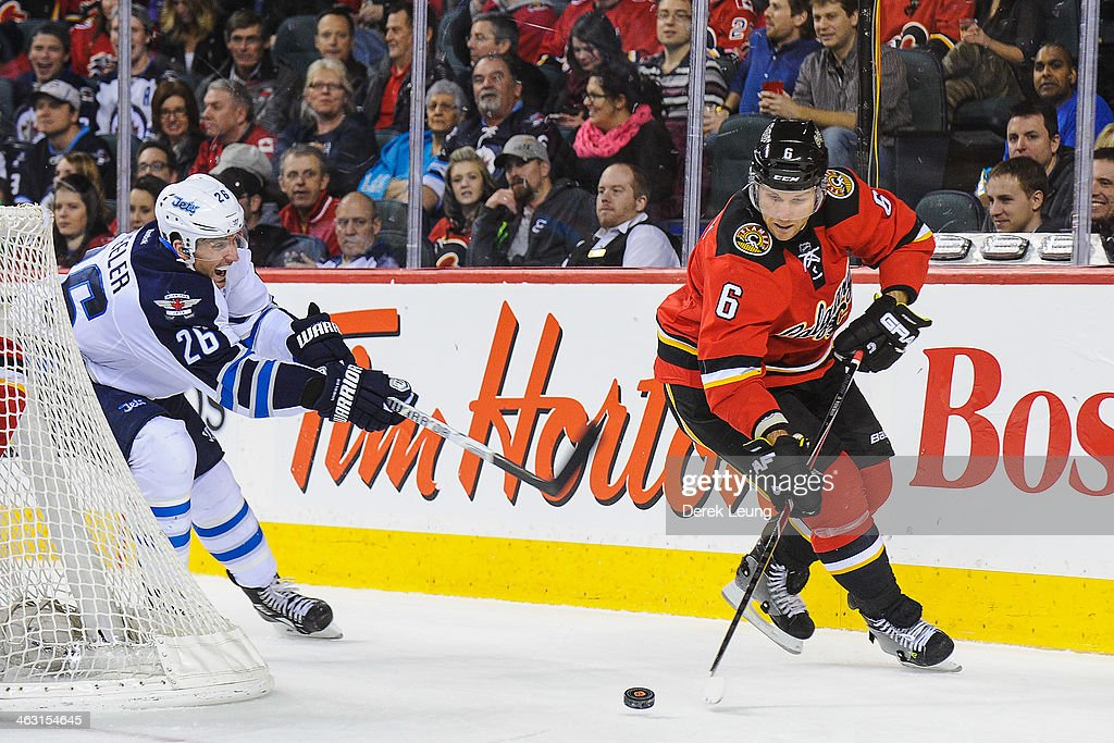 Dennis Wideman #6 of the Calgary Flames skates with the puck past Blake Wheeler #26 of the Winnipeg Jets during an NHL game at Scotiabank Saddledome on January 16, 2014 in Calgary, Alberta, Canada. The Jets defeated the Flames 5-2.