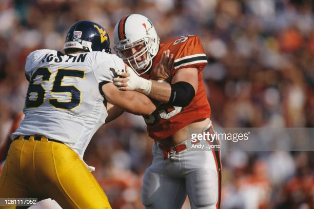 Denny Fortney, Defensive End for the University of Miami Hurricanes blocks Sam Austin of the West Virginia Mountaineers during their NCAA Big East...