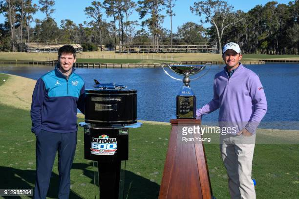 Denny Hamlin and Sam Saunders pose with the Daytona 500 and FedEx Cup trophies on the 17th hole at THE PLAYERS Stadium Course at TPC Sawgrass on...