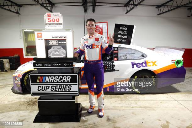 Denny Hamlin, driver of the FedEx Delivering Strength Toyota, celebrates in Victory Lane after winning the rain-shortened NASCAR Cup Series Toyota...