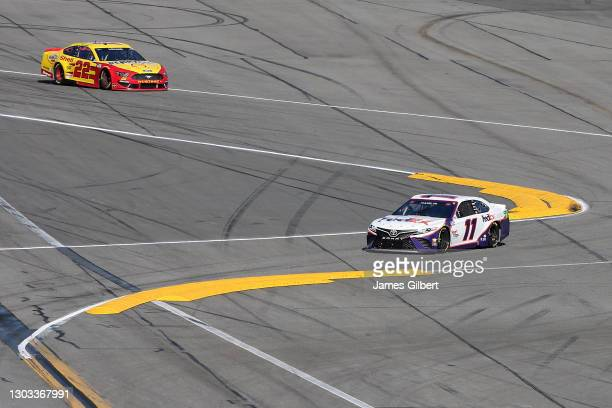 Denny Hamlin, driver of the FedEx Express Toyota, and Joey Logano, driver of the Shell Pennzoil Ford, race during the NASCAR Cup Series O'Reilly Auto...