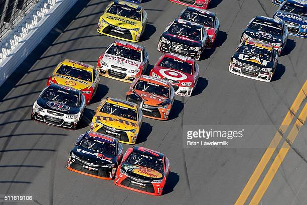 Denny Hamlin driver of the FedEx Express Toyota and Martin Truex Jr driver of the Bass Pro Shops/Tracker Boats Toyota race ahead of the field at the...