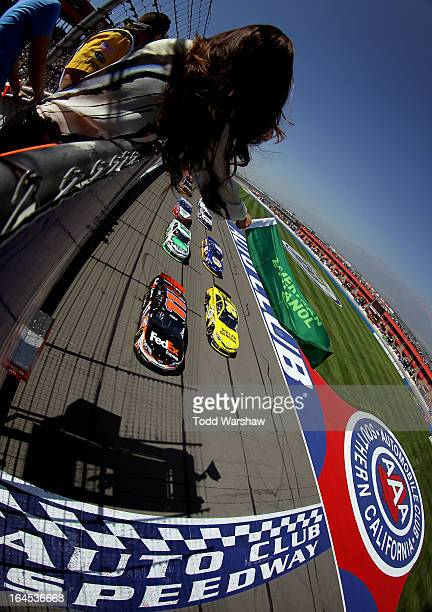 Denny Hamlin driver of the FedEx Express Toyota and Matt Kenseth driver of the Dollar General Toyota lead the field to the green flag to start the...