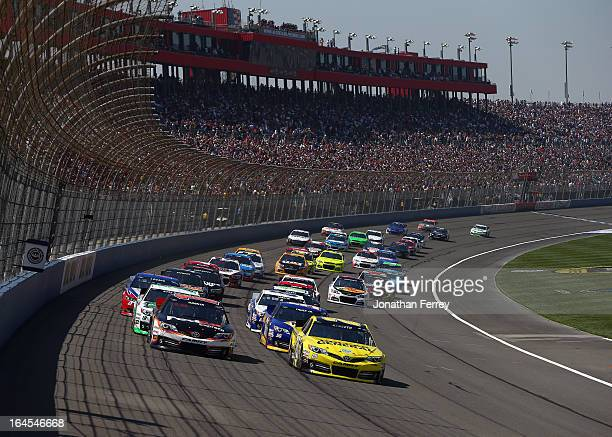 Denny Hamlin driver of the FedEx Express Toyota and Matt Kenseth driver of the Dollar General Toyota lead the field to start the NASCAR Sprint Cup...