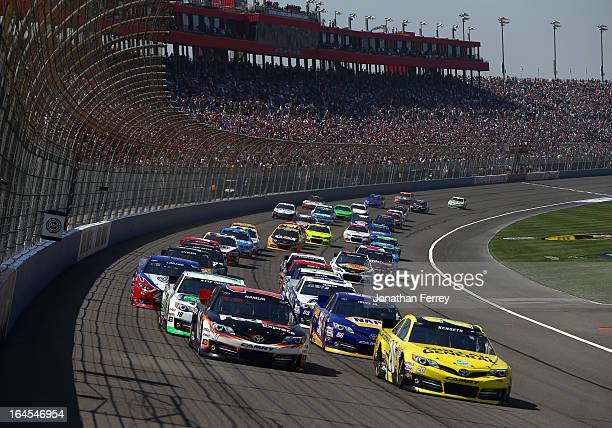 Denny Hamlin driver of the FedEx Express Toyota and Matt Kenseth driver of the Dollar General Toyota lead the field to start of the NASCAR Sprint Cup...