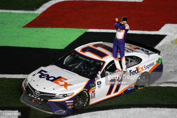 Denny Hamlin driver of the FedEx Express Toyota celebrates after winning the Monster Energy NASCAR Cup Series 61st Annual Daytona 500 at Daytona...