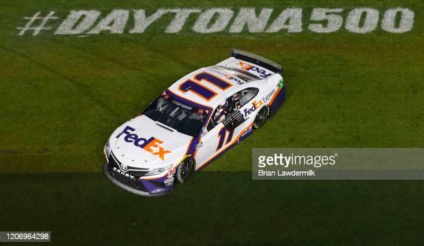 Denny Hamlin, driver of the FedEx Express Toyota, celebrates after winning the NASCAR Cup Series 62nd Annual Daytona 500 at Daytona International...