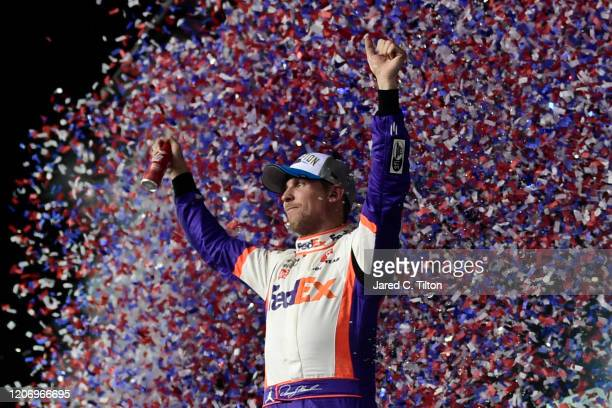 Denny Hamlin driver of the FedEx Express Toyota celebrates in Victory Lane after winning the NASCAR Cup Series 62nd Annual Daytona 500 at Daytona...