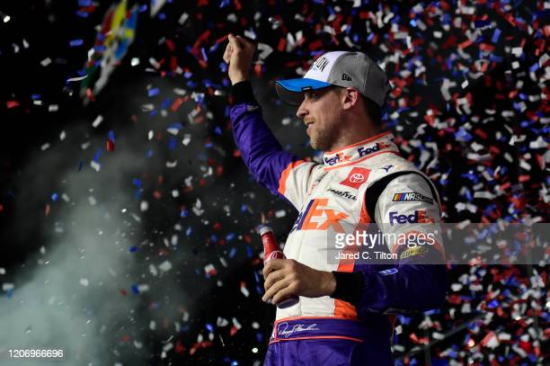 Denny Hamlin, driver of the FedEx Express Toyota, celebrates in Victory Lane after winning the NASCAR Cup Series 62nd Annual Daytona 500 at Daytona...