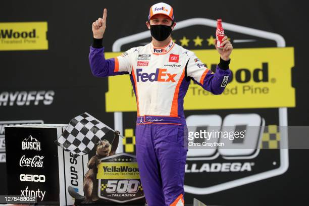 Denny Hamlin, driver of the FedEx Express Toyota, celebrates in Victory Lane after winning the NASCAR Cup Series YellaWood 500 at Talladega...