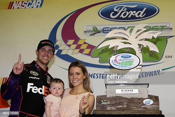 Denny Hamlin driver of the FedEx Express Toyota celebrates in victory lane with his daughter Taylor and Jordan Fish after winning the NASCAR Sprint...