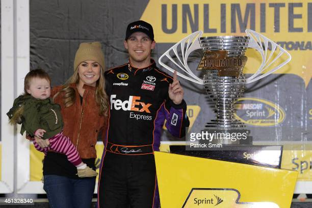 Denny Hamlin driver of the FedEx Express Toyota celebrates in victory lane with Jordan Fish and daughter Taylor during the NASCAR Sprint Cup Series...