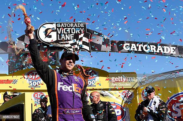 Denny Hamlin driver of the FedEx Express Toyota celebrates in Victory Lane after winning the NASCAR Sprint Cup Series STP 500 at Martinsville...