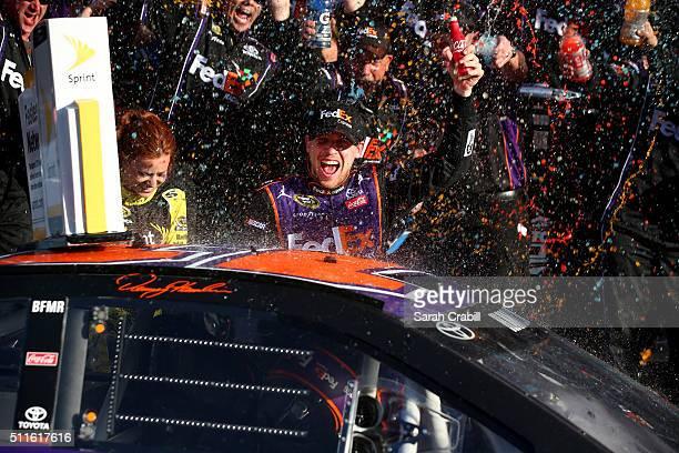 Denny Hamlin driver of the FedEx Express Toyota celebrates in Victory Lane after winning the NASCAR Sprint Cup Series DAYTONA 500 at Daytona...
