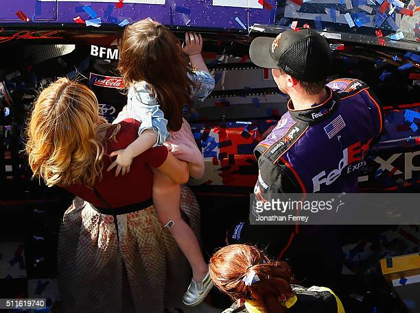 Denny Hamlin driver of the FedEx Express Toyota celebrates in Victory Lane with his wife Jordan Fish and daughter Taylor after winning the NASCAR...