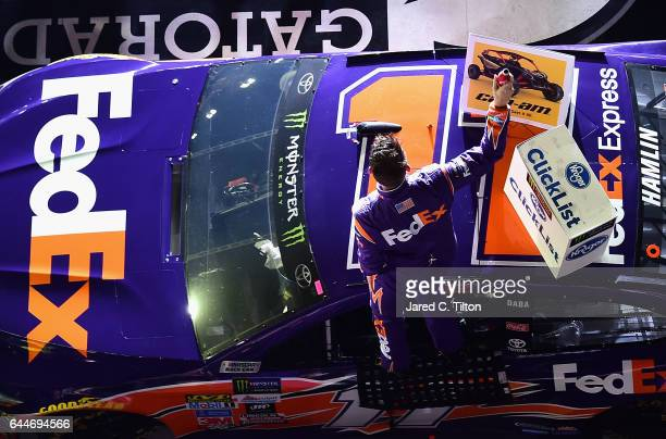 Denny Hamlin driver of the FedEx Express Toyota celebrates in Victory Lane after winning the Monster Energy NASCAR Cup Series CanAm Duel 2 at Daytona...