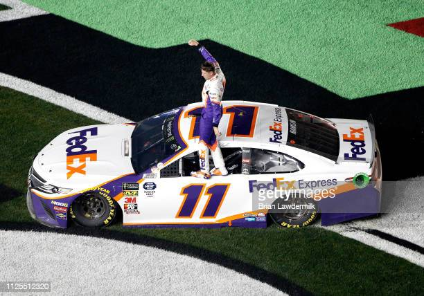 Denny Hamlin driver of the FedEx Express Toyota celebrates winning the Monster Energy NASCAR Cup Series 61st Annual Daytona 500 at Daytona...
