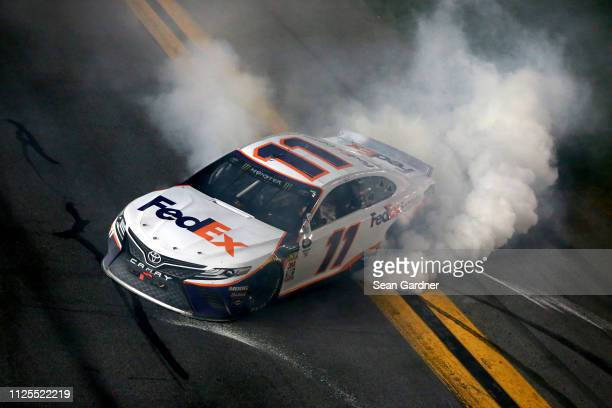 Denny Hamlin driver of the FedEx Express Toyota celebrates with a burnout after winning the Monster Energy NASCAR Cup Series 61st Annual Daytona 500...