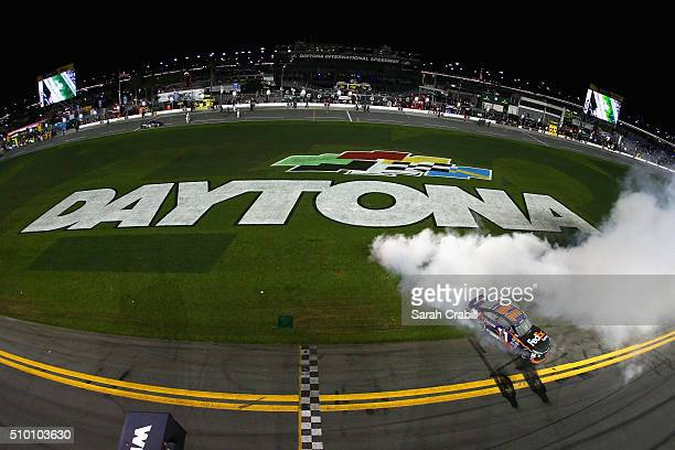 Denny Hamlin driver of the FedEx Express Toyota celebrates with a burnout after winning the NASCAR Sprint Cup Series Sprint Unlimited at Daytona...