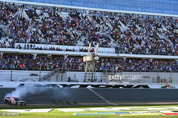 Denny Hamlin driver of the FedEx Express Toyota celebrates with a burnout after winning the NASCAR Sprint Cup Series DAYTONA 500 at Daytona...