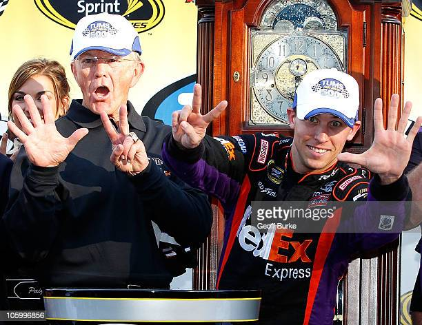 Denny Hamlin driver of the FedEx Express Toyota celebrates with car owner Joe Gibbs in victory lane after winning the NASCAR Sprint Cup Series TUMS...