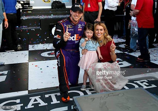 Denny Hamlin driver of the FedEx Express Toyota celebrates with his girlfriend Jordan Fish and daughter Taylor in Victory Lane after putting his feet...