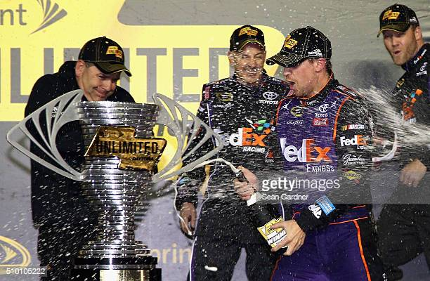Denny Hamlin driver of the FedEx Express Toyota celebrates with members of his crew in Victory Lane after winning the NASCAR Sprint Cup Series Sprint...