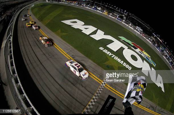 Denny Hamlin driver of the FedEx Express Toyota crosses the finish line winduring the Monster Energy NASCAR Cup Series 61st Annual Daytona 500 at...