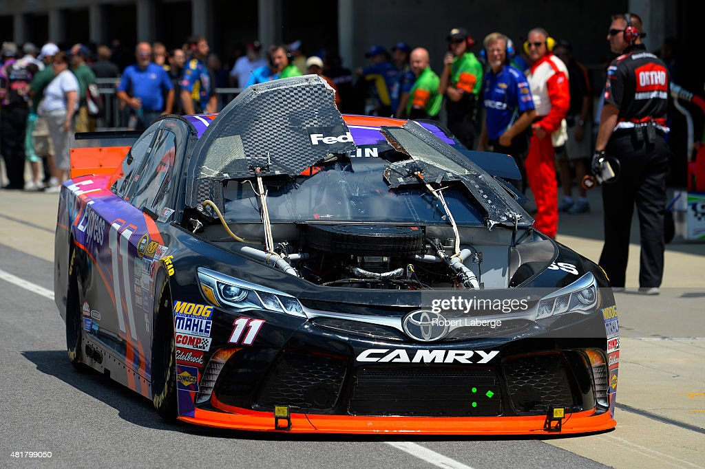 Denny Hamlin, driver of the #11 FedEx Express Toyota, drives back to the garages after his hood flew up during practice for the NASCAR Sprint Cup Series Crown Royal Presents the Jeff Kyle 400 at the Brickyard at Indianapolis Motorspeedway on July 24, 2015 in Indianapolis, Indiana.