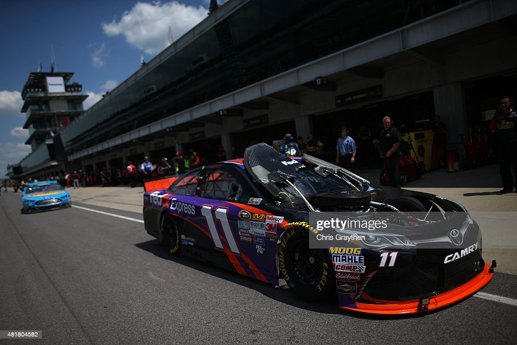 Denny Hamlin, driver of the #11 FedEx Express Toyota, drives through the garage area after his hood flipped up during practice for the NASCAR Sprint Cup Series Crown Royal Presents the Jeff Kyle 400 at the Brickyard at Indianapolis Motorspeedway on July 24, 2015 in Indianapolis, Indiana.