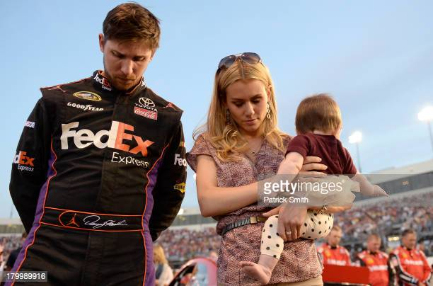 Denny Hamlin driver of the FedEx Express Toyota girlfriend Jordan Fish and their daughter Taylor James Hamlin take part in prerace ceremonies for the...