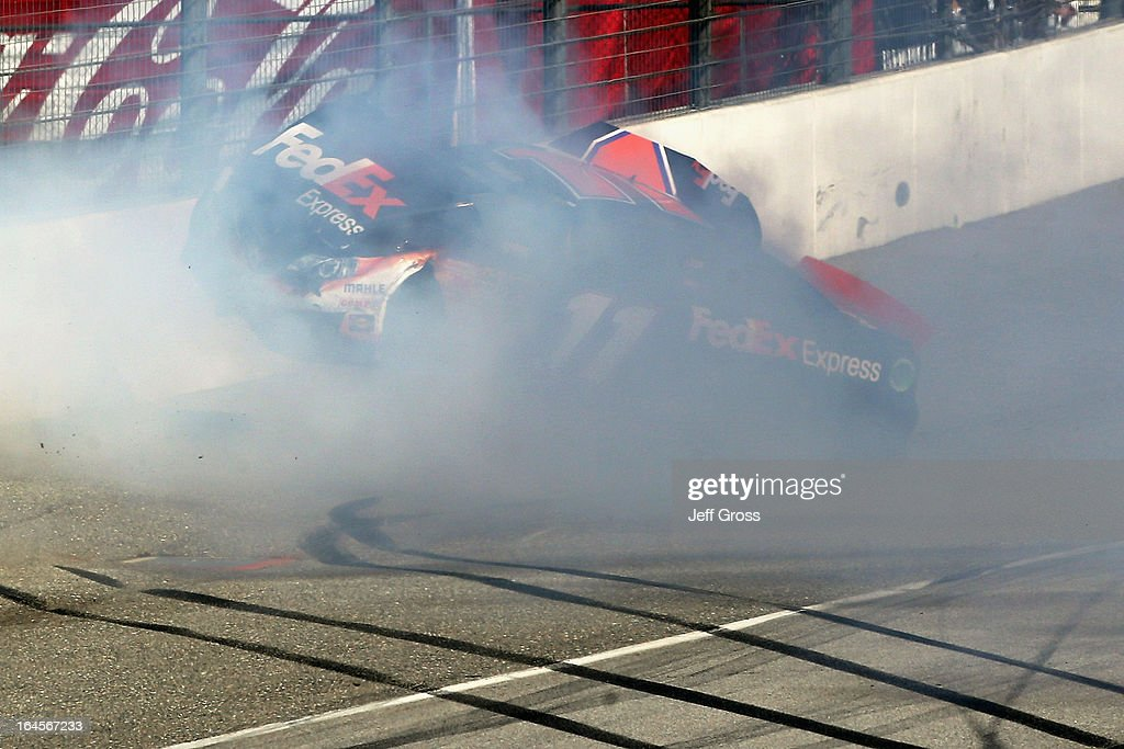 Denny Hamlin, driver of the #11 FedEx Express Toyota, hits the wall after colliding with Joey Logano (not pictured), driver of the #22 AAA Southern California Ford, on the final lap of the NASCAR Sprint Cup Series Auto Club 400 at Auto Club Speedway on March 24, 2013 in Fontana, California.