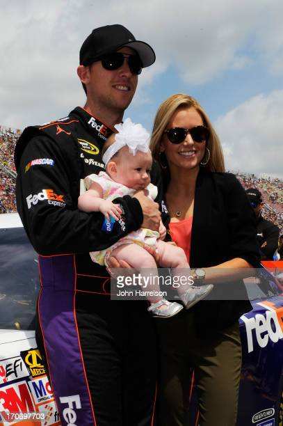 Denny Hamlin driver of the FedEx Express Toyota holds his daughter Taylor James Hamlin as his girlfriend Jordan Fish looks on during prerace...