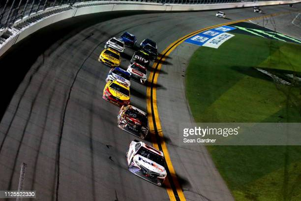 Denny Hamlin driver of the FedEx Express Toyota leads a pack of cars during the Monster Energy NASCAR Cup Series 61st Annual Daytona 500 at Daytona...
