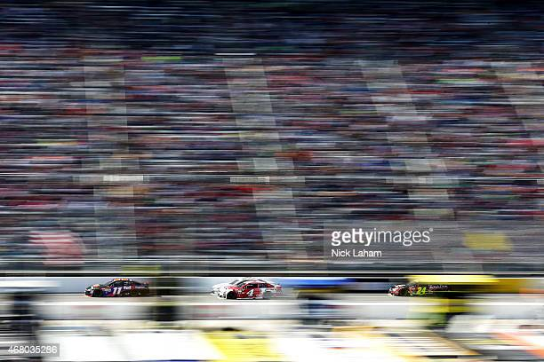 Denny Hamlin driver of the FedEx Express Toyota leads Kevin Harvick driver of the Budweiser/Jimmy John's Chevrolet and Jeff Gordon driver of the...